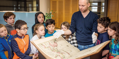 A group of children look at an oversized book handled by a white-gloved employee.