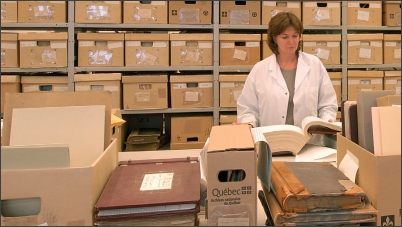 Archiviste devant des boites de documents d'archives.