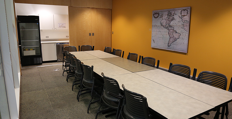Room M.485 laid out with tables and chairs forming a rectangle-shaped layout in the centre of the room.