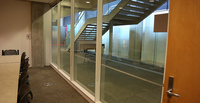 View of the room's glass wall overlooking the Level M hall and the stairs leading to the ground floor.