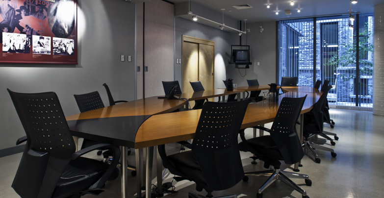 Room 2.28 laid out with a conference room table and ergonomic chairs, well lit by a full-height window.