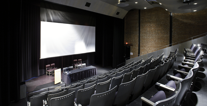 View of the Auditorium's stage, from the upper left side of the stepped row of seats, with lowered projection screen.