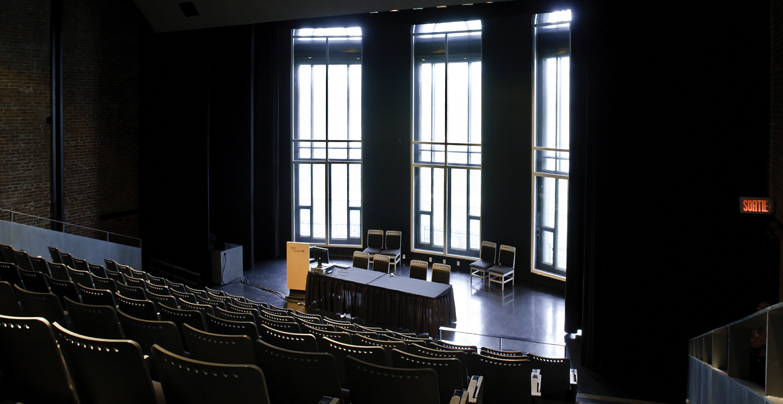 View of the Auditorium's stage, from the upper right side of the stepped row of seats, with uncurtained windows.
