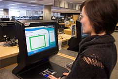 User borrowing a document at self-checkout station.